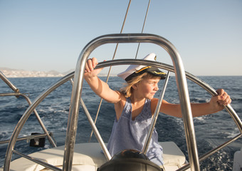 Positive kid in captain hat floating on expensive boat on sea in sunny day