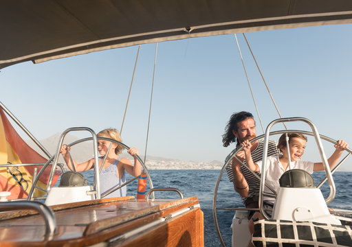 Happy father with children floating on expensive boat on sea and blue sky in sunny day