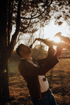 young musician playing the saxophone at sunset