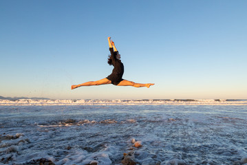 Side view of young dancer in air with legs to sides on sand coast with waving sea and blue sky