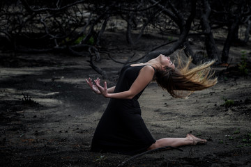 Side view of young ballerina in black wear posing on land between dry woods