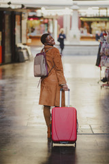 African American elegant woman with baggage walking on street near small shops
