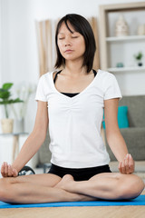 woman meditating at home in lotus position