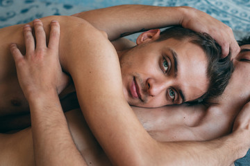 Passionate sexual naked gay couple in an intimate moment lying down in a rug at home