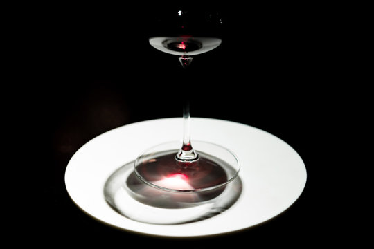 From above glass of red wine on white dish on black background
