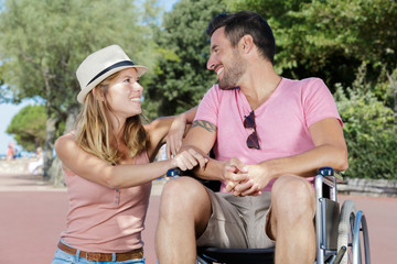 man in wheelchair and his wife enjoying in the park