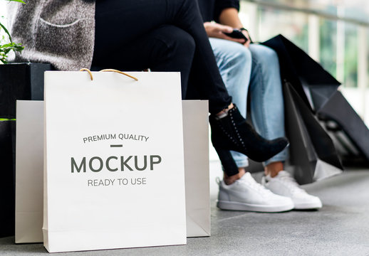 2 People Sitting with Shopping Bags Mockup
