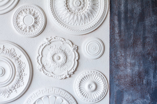A two-color background, gray decorative plaster and a white wall with several white ceiling rosettes