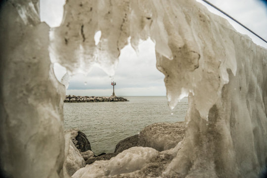 Looking through ice that has formed on edge of rock and in the distance, you'll notice a jetty. Geneva State Park located on the shores of Lake Erie in Ashtabula County, Ohio.