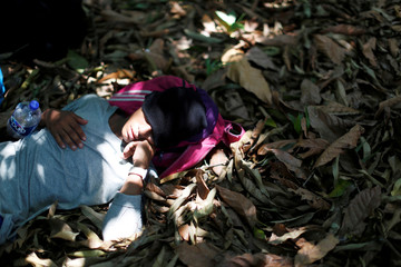 A man belonging to a caravan of migrants from Honduras en route to the United States, sleeps in a forest by a highway in Tuxtla Chico