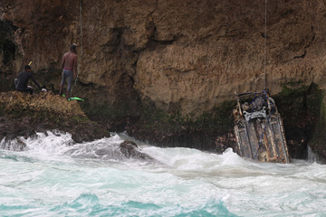 Dominican divers help to recover the wreckage of a car during the search for a rental car presumed to have crashed with U.S. citizens Portia Ravanelle and Orlando Moore, who were due to return to the U.S. on March 27, in Santo Domingo
