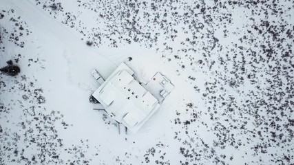 Wall Mural - Aerial view of the mountain house covered in snow in the Winter.