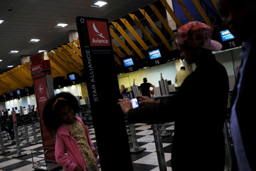 Customers take pictures as they wait to check in at the counter of Avianca airline, at Congonhas airport in Sao Paulo