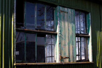 Dilapidated wooden window frame on condemned derelict factory building awaiting demolition