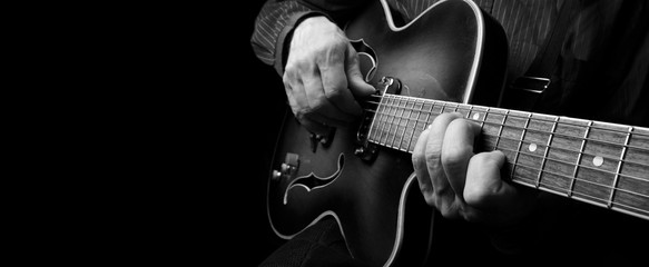 Guitarist hands and guitar close up. playing electric guitar. copy spaces.  black and white. Fotomurales