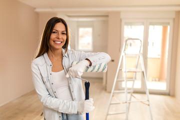 Beautiful woman painting apartment.