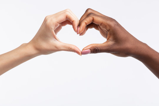 Women with different skin color making heart out of hands