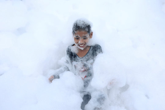 Child plays in a bubble bath during celebrations to mark Thingyan, Myanmar's New Year Water Festival, in Yangon