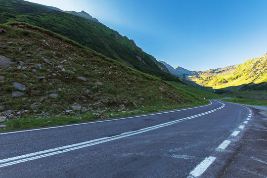 transfagarasan road at sunrise. popular travel destination of romania. beautiful summer landscape in mountains. road winding uphill through gorge with steep rocky cliffs