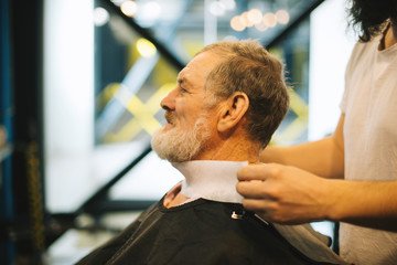 Master prepares client for new haircute, handsome bearded man sitting in chair at Barberchop