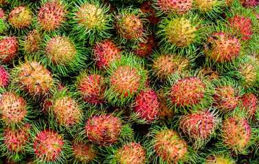 Pile of tropical rambutan fruits. Pink and spiky rambutan are piled on a table at a farmers market. Healthy fruits rambutans background.