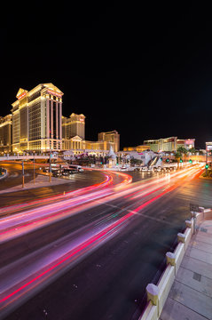 Las Vegas, Nevada / USA - 09.03.2015: Cars at the junction of South Las Vegas Boulevard and West Flamingo Road in front of Caesars Palace on the Las Vegas strip at night.