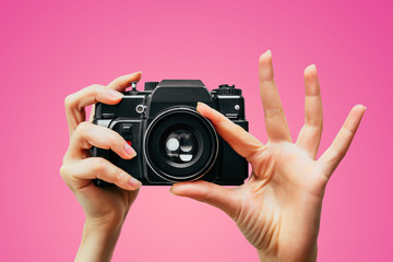 Vintage Camera in female hand. A photo. Photographer. Manual focus. Colored background. Pink