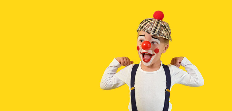 Portrait funny child clown.Cheerful boy,costume,red nose,makeup.Emotional face little comic kid.Happy baby isolated yellow background. concept birthday, holiday, humor. studio,blank,banner,copy space