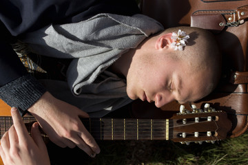 Overhead view of young man is lying down under a tree with his guitar in a sunny day of spring