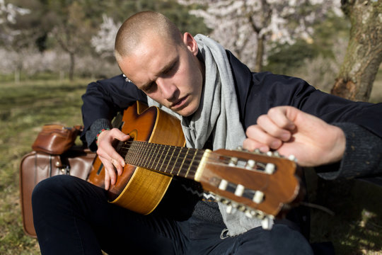 Side view of young shaved man sitting on the grass tuning his guitar in a sunny day