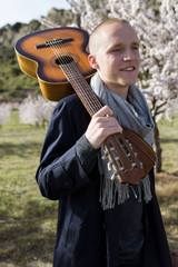 Portrait of young shaved man with a guitar and trench coat in the middle of a field in a sunny day of spring