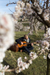 View through a flowers of a tree of young shaven man with a trench coat is sitting on the grass and playing his guitar