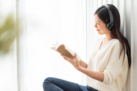 Young beautiful Asian woman listen song music at home, happy lifestyle concept