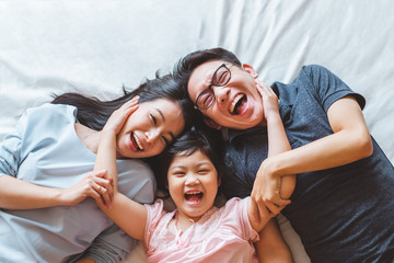 Happy Asian family laying on bed smile, top view