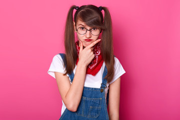 Childish charismatic young lady puts her hand on face, thinking over her plans, makes frowny face. Funny girl with bangs and long pigtails stands straight isolated over bright pink background.