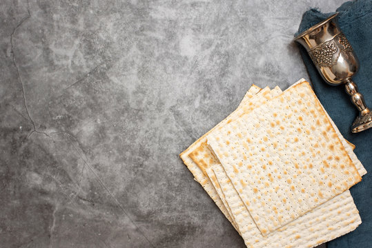 Jewish Passover holiday. Matza and glass for wine on a grey background. Top view. With copy space