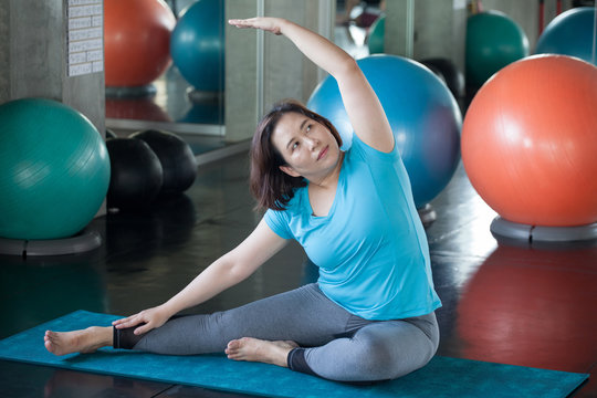 asian Senior woman Doing yoga in fitness gym. aged lady exercising.  Old female workout .Mature fat sport training.rehabilitation.elderly Overweight Healthy lifestyle Weight loss concept