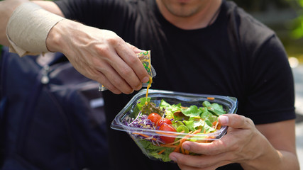 Putting Italian Dressing on Healthy Fresh Salad in Plastic Container