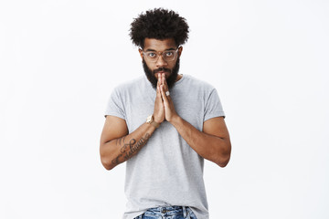 Student bowing to sensei. Portrait of devoted and serious-looking calm african american adult bearded guy in glasses with tattoos and piercing nodding making namaste greeting with hands together