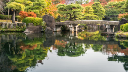 Pictorial scene at Koko-en Gardens in Himeji, Japan with the classical bridge over the pond and spectacular autumn foliage reflected in the water.