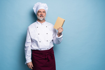 Portrait of a professional chef in uniform holding recipe book and looking at camera on light blue.