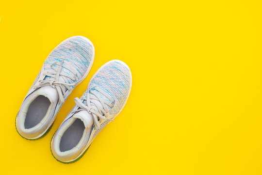Pair of trendy sport sneakers on yellow background. Top view with copy space.
