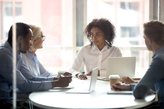 Serious african american female leader talking at diverse group meeting