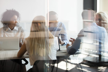 Multicultural employees talking at team meeting sit at conference table