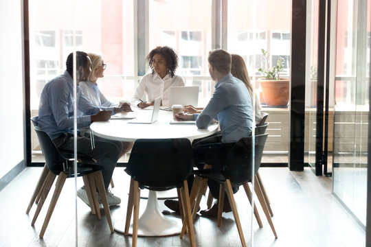 Multiracial business team people talking sitting at office boardroom table