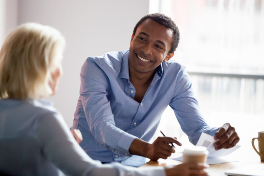 Smiling african american manager talking with client at business meeting