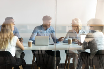 Diverse business people negotiating at table behind closed glass door