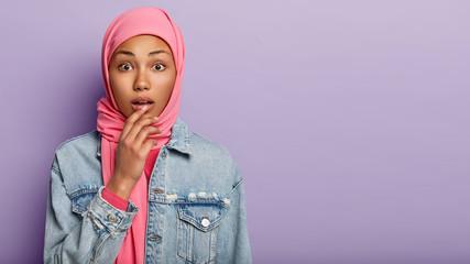 Horizontal shot of impressed surprised Arab woman looks with wonder, hears unbelievable news, wears...