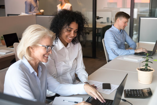 Smiling old mentor helping african intern with laptop in office