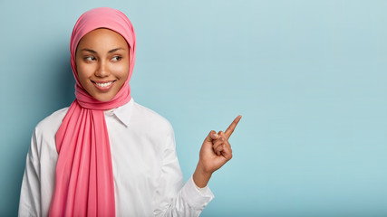 Smiling black woman has cheerful expression, points away with fore finger, shows blank space on right corner, has modest look, wrapped in pink veil, isolated over blue background. Look at this